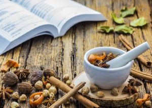 A photo of Mortar Grinder Herb and herbal with Herbal Pharmacopoeia background on wood table, Selective focus, Soft focus
